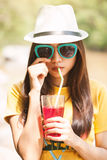 Woman drinking iced drinks outdoors with sand by the sea Royalty Free Stock Image