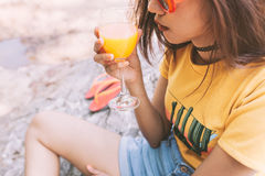 Woman drinking iced drinks outdoors with sand by the sea Royalty Free Stock Photography