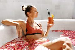 Woman Drinking Juice Cocktail, Relaxing Spa Flower Bath. Summer Stock Image