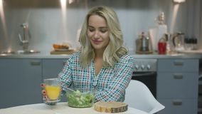 Woman drinking juice and eating salad stock footage