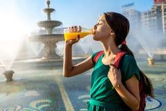 Woman drinking juice near the fountain Stock Image