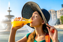 Woman drinking juice near the fountain Royalty Free Stock Image