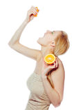 Woman drinking juice  from an orange fruit Royalty Free Stock Photos