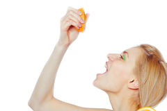 Woman drinking juice  from an orange fruit Stock Photo