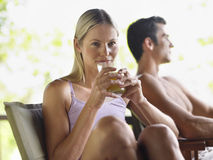 Woman Drinking Juice By Shirtless Man. Portrait of a young women drinking juice with shirtless men in background Stock Images