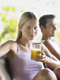 Woman Drinking Juice By Shirtless Man. Portrait of a young women drinking juice with shirtless men in background Royalty Free Stock Images
