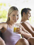 Woman Drinking Juice By Shirtless Man. Portrait of a young women drinking juice with shirtless men in background Royalty Free Stock Photography
