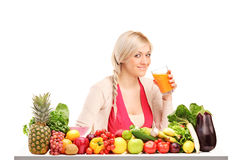 Woman drinking juice, on a table full of food Stock Photography