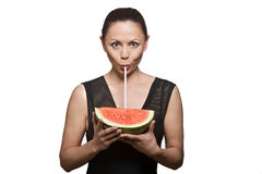 Woman drinking juice through watermelon Stock Image