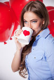 Woman drinking from a love mug Stock Images