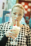Woman drinking milk shake in diner. Royalty Free Stock Photos