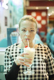 Woman drinking milk shake in diner. Royalty Free Stock Images