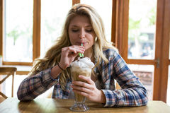 Woman drinking milkshake with straw in cafe Stock Images