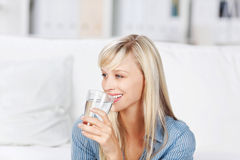 Woman drinking mineral water. Smiling healthy woman drinking a large glass of bottled mineral water to quench her thirst stock image