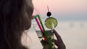 Woman drinking mojito with a straw stock footage
