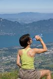 Woman drinking on mountain. Woman drinking of water to the bottle Royalty Free Stock Photo