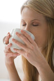 Woman drinking from a mug Stock Photography