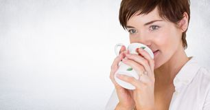 Woman drinking from mug against white wall. Digital composite of Woman drinking from mug against white wall Stock Image