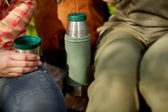 Woman drinking a mug of coffee from a flask. Woman drinking a mug of hot coffee from a thermal flask as she relaxes outdoors chatting to a friend in a close up Royalty Free Stock Image