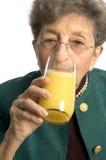 Woman drinking orange juice stock images