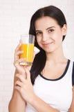 Woman drinking orange juice Beautiful mixed-race Asian, Caucasian model. Woman drinking orange juice smiling showing oranges. Young beautiful mixed-race Asian stock images