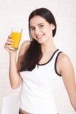 Woman drinking orange juice Beautiful mixed-race Asian, Caucasian model. Woman drinking orange juice smiling showing oranges. Young beautiful mixed-race Asian royalty free stock image