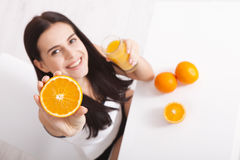 Woman drinking orange juice Beautiful mixed-race Asian, Caucasian model. Woman drinking orange juice smiling showing oranges. Young beautiful mixed-race Asian stock image