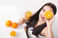 Woman drinking orange juice Beautiful mixed-race Asian, Caucasian model. Woman drinking orange juice smiling showing oranges. Young beautiful mixed-race Asian royalty free stock photography