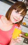 Woman drinking orange juice at home Stock Photos