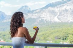 Woman is drinking orange juice on the hotel balcony. Royalty Free Stock Images