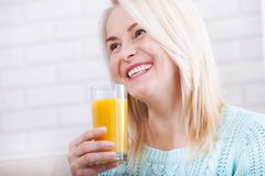 Woman drinking orange juice smiling. Beautiful middle aged Caucasian model face closeup. Royalty Free Stock Photos