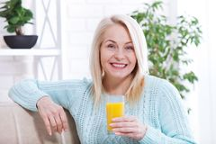 Woman drinking orange juice smiling. Beautiful middle aged Caucasian model face closeup. Royalty Free Stock Photography