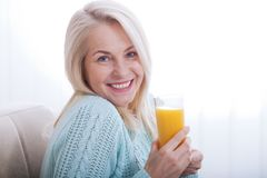 Woman drinking orange juice smiling. Beautiful middle aged Caucasian model face closeup. Stock Photography