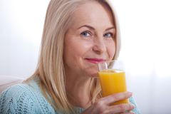 Woman drinking orange juice smiling. Beautiful middle aged Caucasian model face closeup. Royalty Free Stock Image