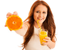 Woman drinking orange juice smiling showing oranges. Young beaut Royalty Free Stock Photo