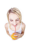 Woman drinking an orange with straw Stock Photos
