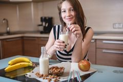 Woman drinking organic almond milk holding a glass in her hand in the kitchen. Diet healthy vegetarian product stock photo