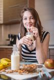 Woman drinking organic almond milk holding a glass in her hand in the kitchen. Diet healthy vegetarian product stock image