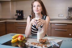 Woman drinking organic almond milk holding a glass in her hand in the kitchen. Diet vegetarian product stock photography