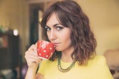 Woman Drinking from Red Polka Dot Tea Mug Royalty Free Stock Photography