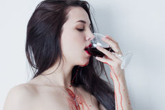 Woman drinking red wine, which runs down her arms and chest Royalty Free Stock Photography