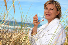Woman drinking  by the seaside Stock Images