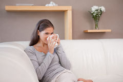 Woman drinking some coffee on the sofa Royalty Free Stock Photos