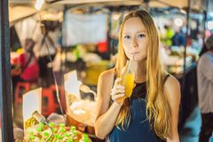 Woman drinking sugar cane juice on the Asian market.  stock image