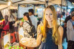Woman drinking sugar cane juice on the Asian market.  royalty free stock images