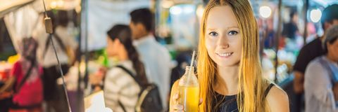 Woman drinking sugar cane juice on the Asian market BANNER, LONG FORMAT. Woman drinking sugar cane juice on the Asian market. BANNER, LONG FORMAT stock photos