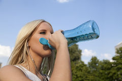 Woman drinking in summer. Woman drinking from botte during exercise Stock Photography