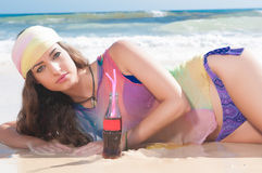 Woman drinking on a sunny beach Royalty Free Stock Photography