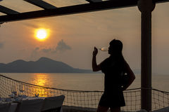 Woman drinking at sunset Stock Images