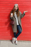 Woman drinking take away coffee and holding copyspace on palm. Surprised young woman drinking take away coffee and holding copyspace on palm over red wall Royalty Free Stock Image